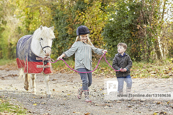 Boy and sister leading pony along country lane