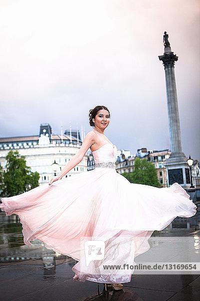 Porträt einer jungen Frau  die in der Abenddämmerung im Abendkleid tanzt  Trafalgar Square  London  UK