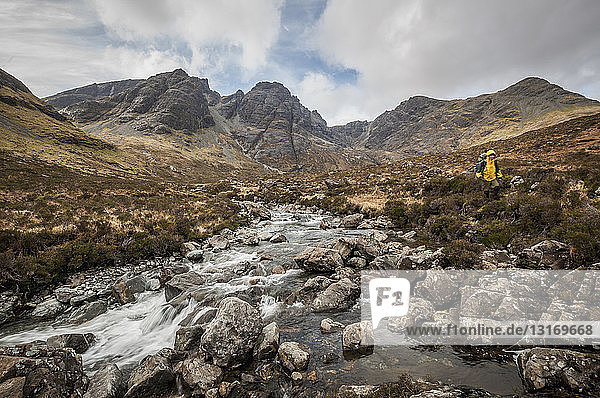 'Hiker next to a river with the Black Cuillin's ''Bla Bheinn'' Mountain  Isle of Skye  Scotland'