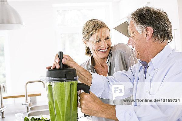 Ehepaar bereitet in der Küche grünen Gemüsesmoothie zu