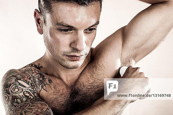 Studioaufnahme eines mittleren erwachsenen Mannes  der ein Deodorant aufträgt