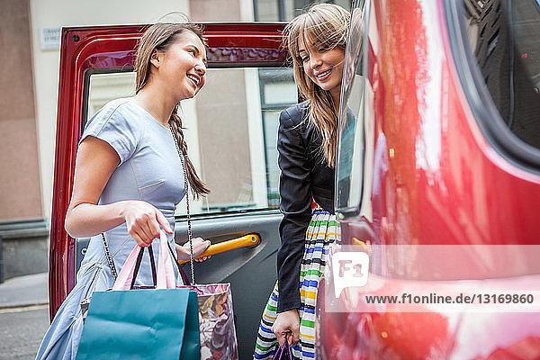 Junge Frauen steigen in ein Taxi ein und tragen Einkaufstaschen