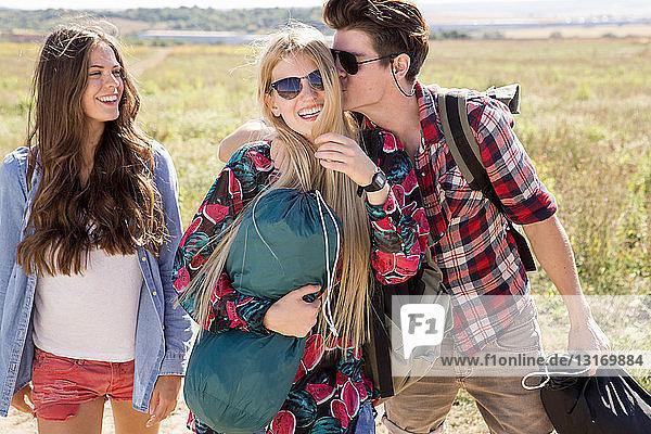 Drei Freunde beim Wandern  Mann küsst Frau