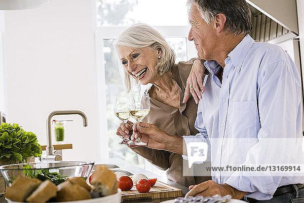 Älteres Ehepaar trinkt in der Küche ein Glas Wein