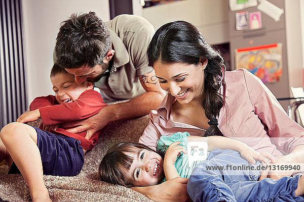Familie mit zwei Kindern  die auf dem Sofa spielen