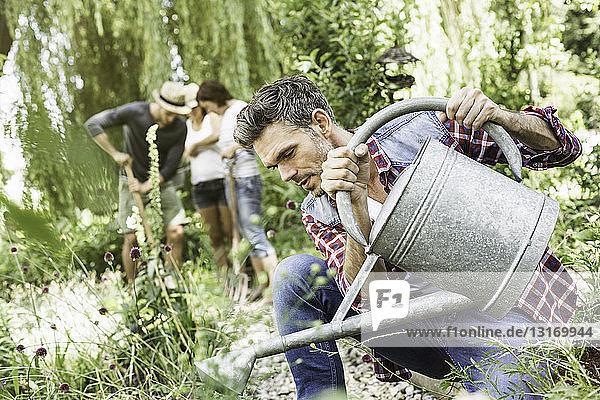 Mann gießt Pflanzen im Garten