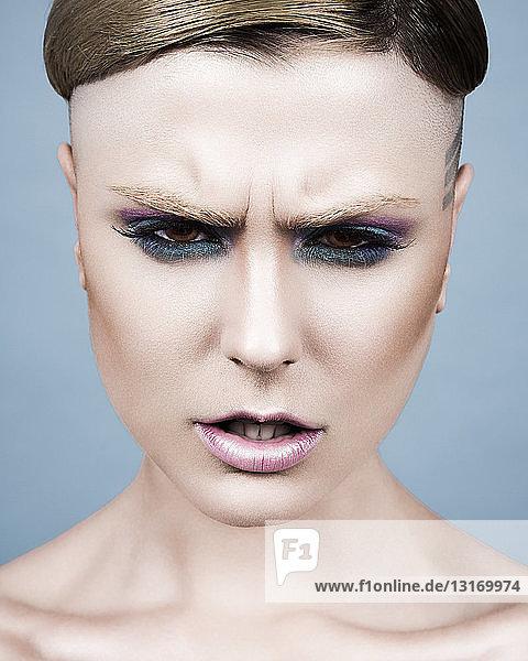 Junge Frau mit kurzer Frisur  dunklem Augen-Make-up und wütendem Gesichtsausdruck