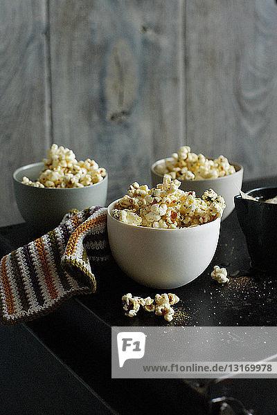 Schalen mit aromatisiertem Popcorn auf dem Tisch