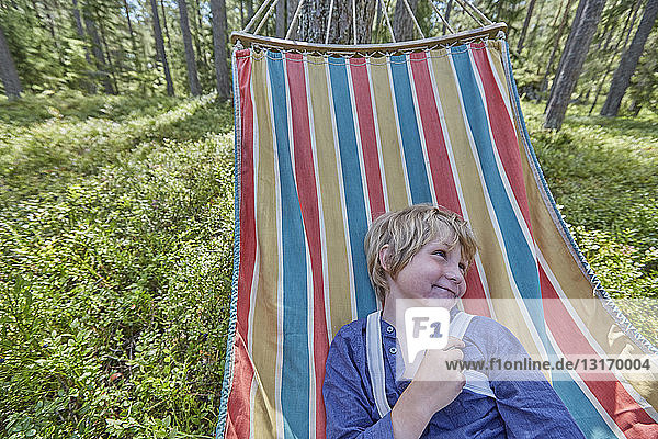 Mischievous boy dressed in retro clothing on forest hammock