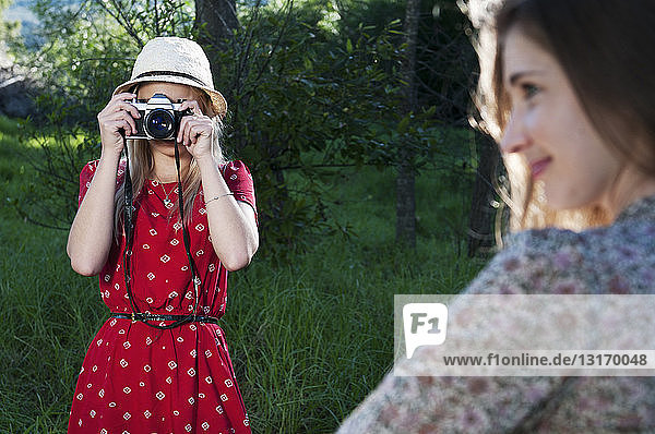 Young woman taking photograph of friend