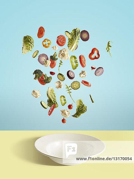 Fresh sliced vegetables and salad leaf falling into bowl