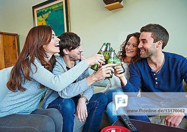 Gruppe von Freunden schaut Sport im Wohnzimmer