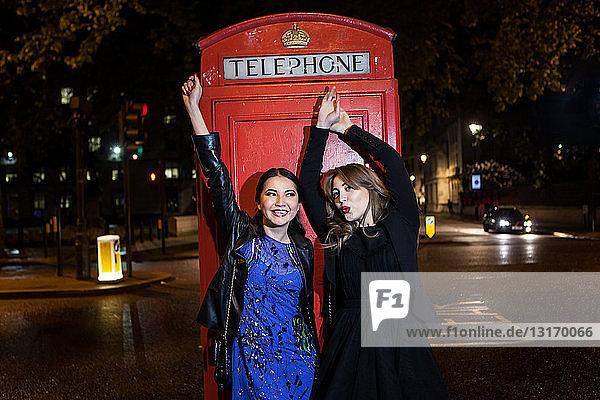 Zwei junge Freundinnen tanzen nachts vor einer roten Telefonzelle  London  UK