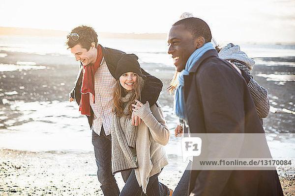 Zwei erwachsene Paare gehen am Strand spazieren