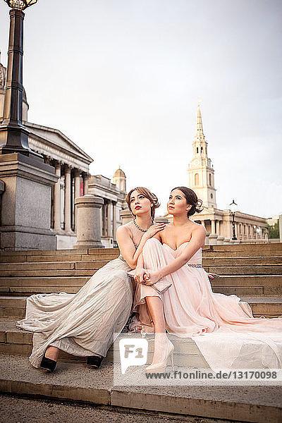 Porträt zweier weiblicher Modelle  die auf Stufen posieren  Trafalgar Square  London  UK