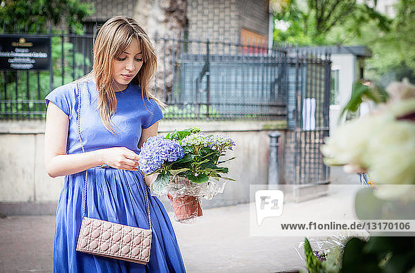 Junge Frau hebt Topfpflanze auf