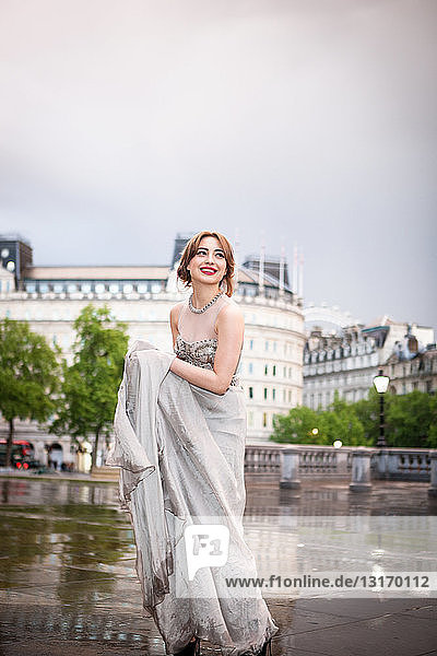 Junge Frau  die ein nasses Abendkleid hochhält  Trafalgar Square  London  Großbritannien