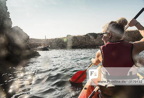 Rückansicht einer Seekajakfahrerin  Menorca  Balearen  Spanien Rückansicht einer Seekajakfahrerin, Menorca, Balearen, Spanien