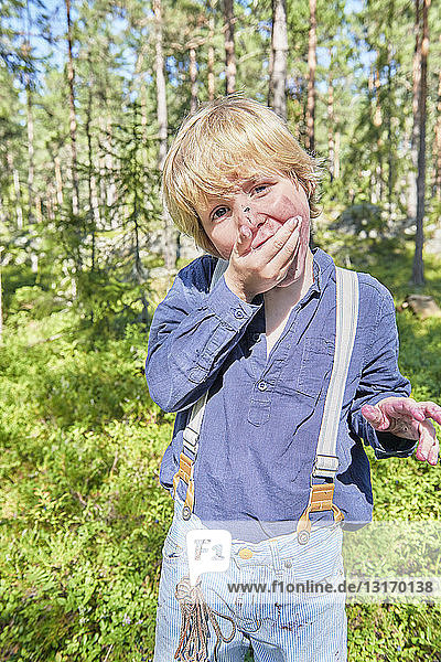 Portrait of young boy wearing retro clothes eating berries in forest