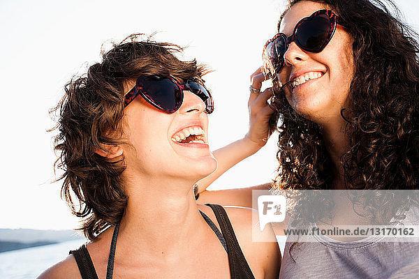 Lachende Frauen mit Sonnenbrille am Strand