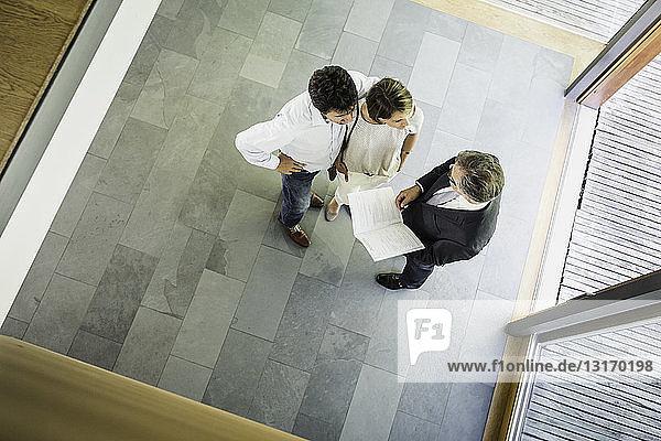 Draufsicht auf Immobilienmakler und reifes Paar im neuen Haus