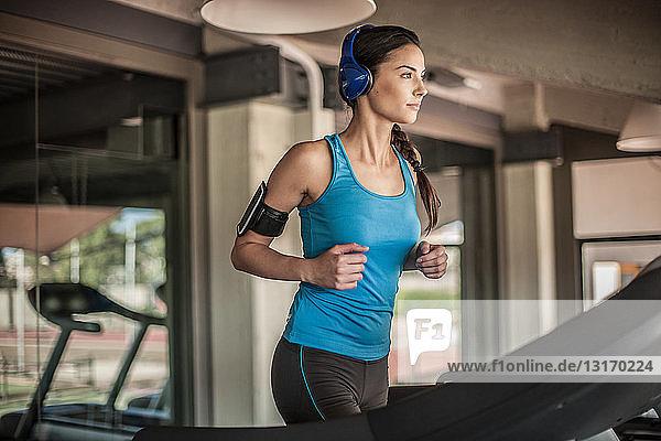Junge Frau läuft auf dem Laufband