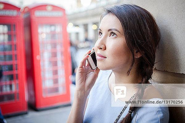 Junge Frau am Smartphone  vor der roten Londoner Telefonzelle
