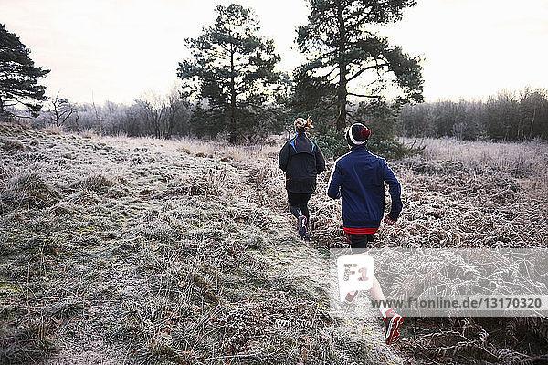 Rückansicht von Mutter und Sohn beim Laufen auf frostigem Grasland