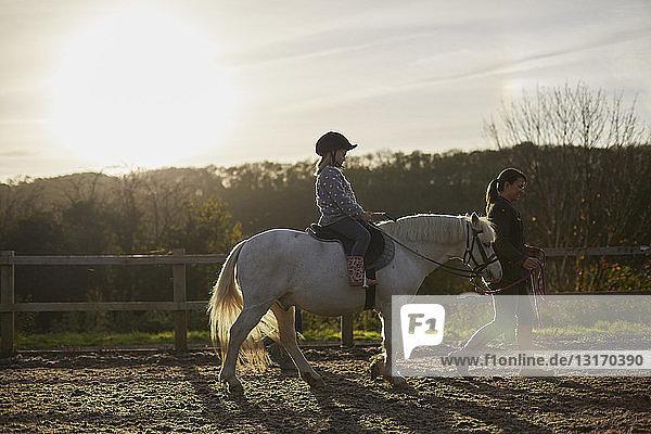 Ausbilderin führt Mädchen beim Ponyreiten auf dem Reitplatz