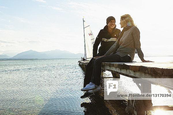 Reifes Paar sitzt lächelnd auf dem Steg