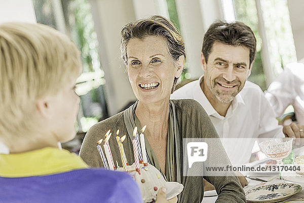 Boy handing birthday cake to grandmother at party