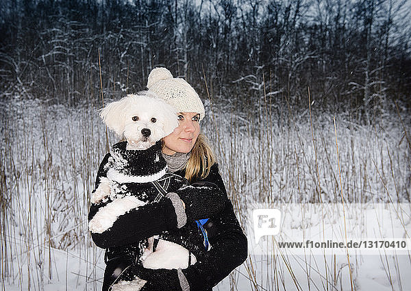 Mid adult woman with pet dog in snowy landscape