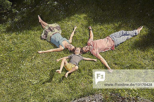 Mutter  Vater und Sohn  im Garten  auf dem Rasen liegend  entspannend