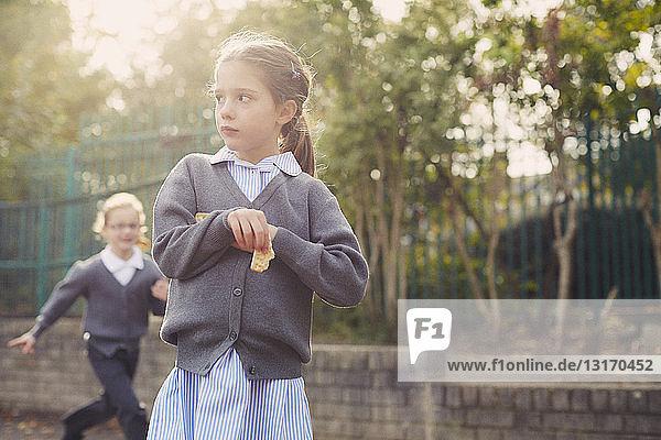 Elementary schoolgirl eating cracker in playground