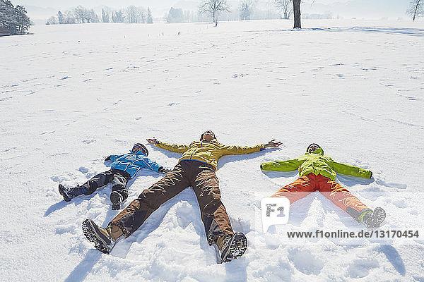 Mutter und Söhne machen Schneeengel im Schnee