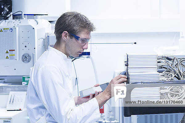 Male scientist adjusting control panel in laboratory