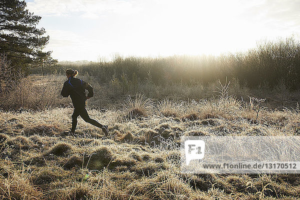 Rear view of mature woman running on frosty grassland