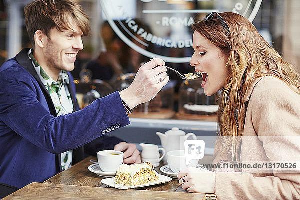 Mann füttert Freundin mit Kuchen im Bürgersteig-Café  London  Großbritannien