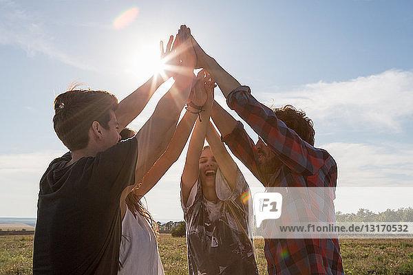Vier Freunde halten sich mit erhobenen Armen an den Händen