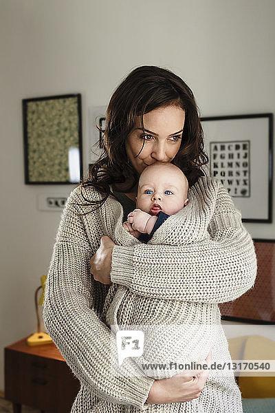 Frau küsst kleinen Sohn und wickelt ihn in ihre Strickjacke