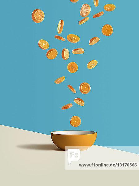 Fresh sliced oranges dropping into orange bowl