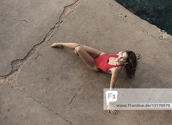 High angle portrait of young woman posing in red bathing costume on pier