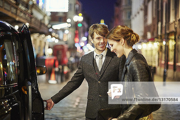 Couple getting into taxi cab  London  England