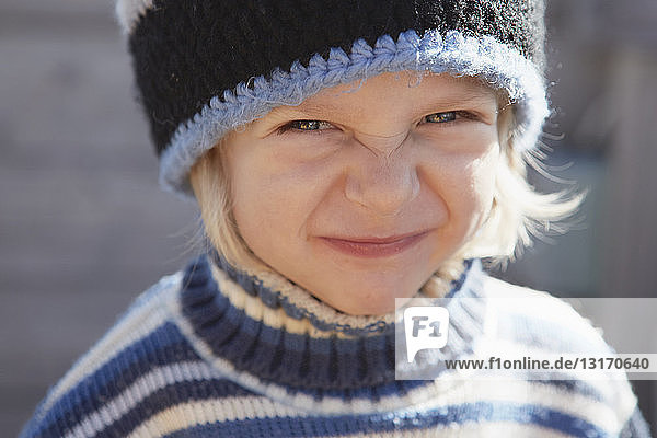 Portrait of young boy wearing woolly hat and jumper  making face