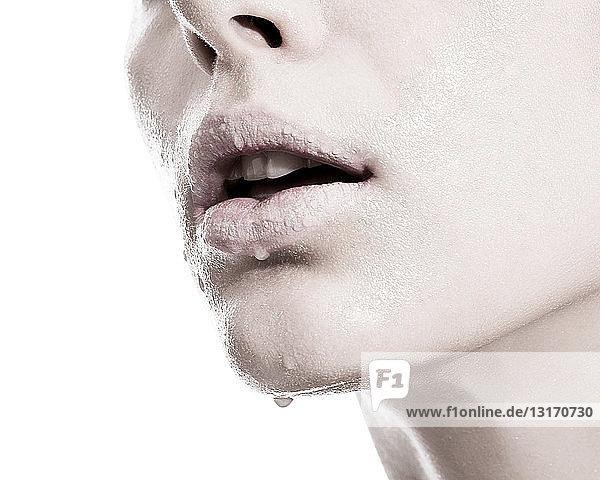 Frau mit Flüssigkeitströpfchen auf den Lippen  Nahaufnahme