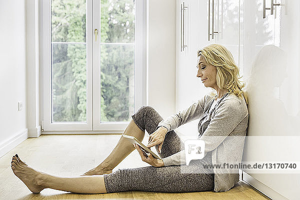 Mature woman sitting on floor at home using touchscreen on digital tablet