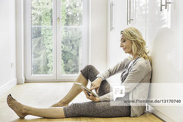 Reife Frau sitzt zu Hause auf dem Boden und benutzt Touchscreen auf digitalem Tablet
