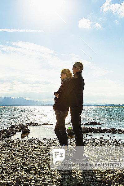 Ein erwachsenes Paar steht am See  umarmt sich  schaut auf die Aussicht