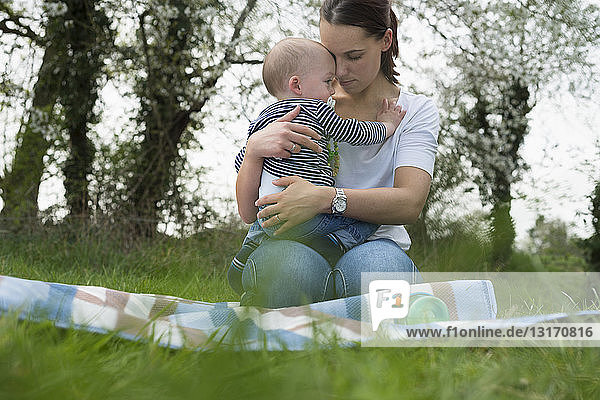 Young mother hugging baby son on picnic blanket in field