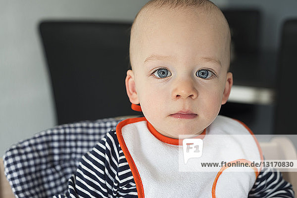 Portrait of staring baby boy in high chair